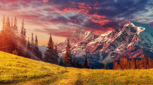 Awesome Alpine Highlands In Sunny Day. Scenic Image Of Fairy-tale Landscape With Colorful Sky Under Sunlit, Over The Majestic Rock Mountains. Wild Area. Megical Natural Background. Creative Image