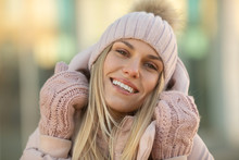 Portrait Of A Beautiful Young Model In Pink Knitted Hat  And Mittens. Beautiful Natural Young Smiling Blonde Woman Wearing Knitted Gloves.