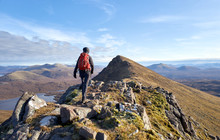 A Hiker Walking Towards The Summit Of Sgurr An Tuill Bhain Along A Narrow Rocky Ridge In The Scottish Highlands On A Sunny Winters Day.