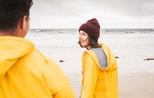 Young Woman Wearing Yellow Rain Jackets And Walking Along The Beach, Bretagne, France