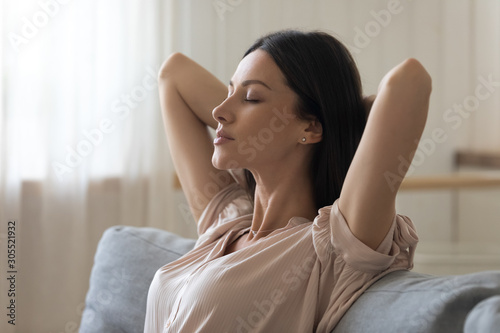 Fototapeta Calm tired young woman lounge on sofa with eyes closed obraz