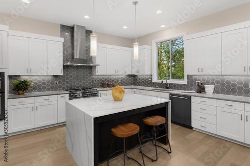 Fototapeta Beautiful kitchen in new luxury home with waterfall island, quartz counter tops, farmhouse sink, and hardwood floors. obraz