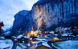 amazing touristic alpine village at night in winter with famous church and Staubbach waterfall  Lauterbrunnen  Switzerland  Europe