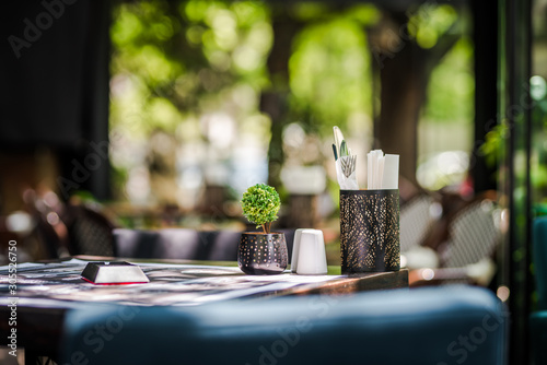 Fototapeta Simple and elegant outdoor restaurant table set up on  green background obraz