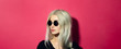 canvas print picture - Close-up portrait of young blonde serious girl with glance away, wearing black round sunglasses and shirt, isolated on pink coral background.