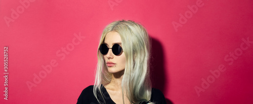 Close-up portrait of young blonde serious girl with glance away, wearing black round sunglasses and shirt, isolated on pink coral background Fototapet