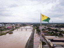 Aerial Drone View Of Acre River And Flag In The Amazon. Rio Branco City Center Buildings, Houses, Streets, Bridges On Cloudy Day. Brazil. Concept Of Environment, Ecology, Climate Change And Travel.