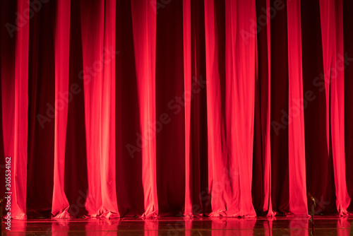 Fotografie, Obraz  Theater red curtain with spot lighting and reflections on the floor
