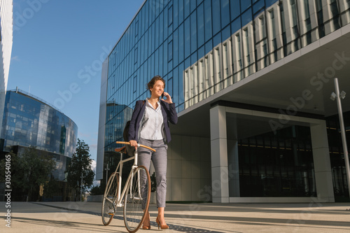 Positive businesswoman with bike smiling and speaking on smartphone while walking outside contemporary building on sunny day on city street - 305540165