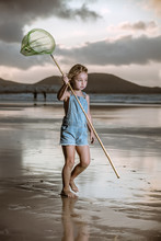 Pensive Adorable Girl With Green Butterfly Walking Barefoot On Seaside In Gray Cloudy Day