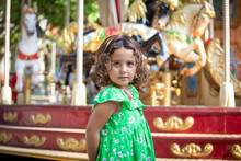 Side View Of Pensive Calm Kid In Green Casual Clothes Looking Away While Standing Against Colorful Rotating Attraction With Carnival Horses In Amusement Park