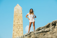 Curly Haired Female Tourist In Loose Light Shirt Looking At Camera While Standing On Cliff Arms Akimbo And Big Rocked Obelisk On Background