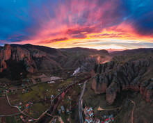 Vibrant Evening Sky Above Peaceful Rocky Hills And Remote Buildings