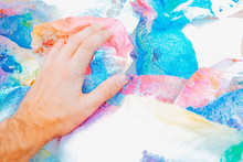 From Above Crop Artist Touching Bright Blue Pink Colored Crumpled Soft Sheet Of Paper On Table, Texas