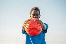 Black Teenager In Blue T-shirt Carrying Red Ball In Outstretched Arms And Looking At Camera Against Cloudless Sky