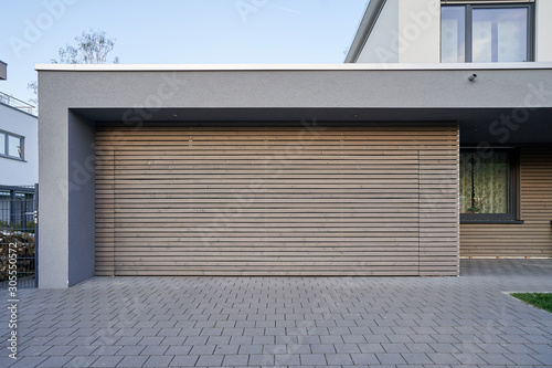 Fototapeta A modern Scandinavian-style garage with a wood-paneled garage door