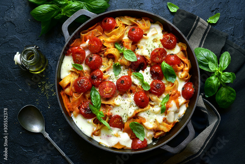 Pasta casserole with tomatoes and mozzarella cheese in a cast iron pan Fototapete