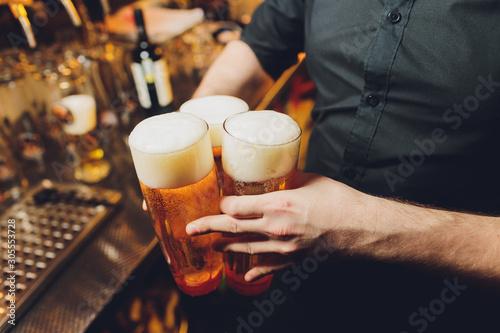 Fototapeta Waiter serving glasses of cold beer on the tray. obraz