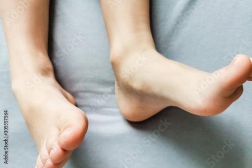 Fotografía Children's bare feet. Child's bare feet on a gray bed