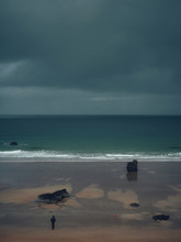 Man Walking Dog On The Beach Before Storm