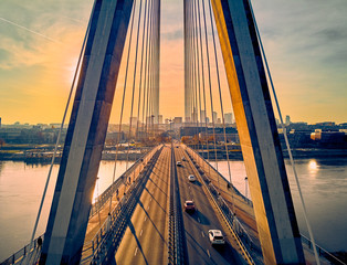 Fototapeta Industrialny Beautiful panoramic aerial drone sunset view to Warsaw city center with skyscrapers and Swietokrzyski Bridge (En: Holy Cross Bridge) - is a cable-stayed bridge over the Vistula river in Warsaw, Poland