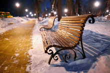 Winter Park With Benches Covered With Snow In The Evening.