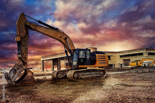 Fotomural  Excavating machinery at the construction site, sunset in background