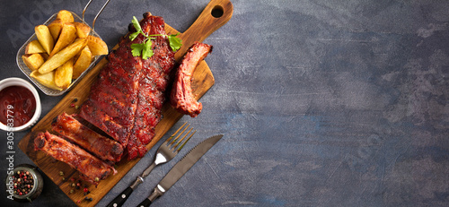 Pork loin ribs served on chopping board and potato wedges Canvas Print