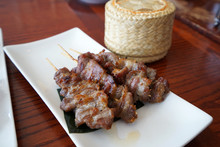 Close Up Barbecue Pork Skewers Served With A Wooden Basket Of Sticky Rice ,Thai Recipe