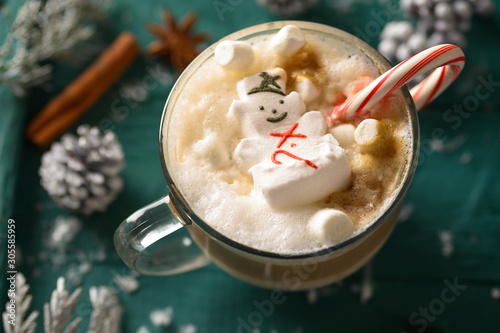 Foto auf Leinwand Schokolade Christmas composition, mug with hot chocolate with melted snowman marshmallows and caramel. horizontal frame over green background