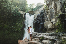 Young Couple In Love Kissing With Amazing View Of Tegenungan Cascade Waterfall. Happy Together, Honeymoon In Bali. Travel Lifestyle.