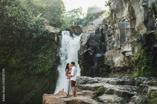 Young couple in love kissing with amazing view of Tegenungan cascade waterfall Fototapeta