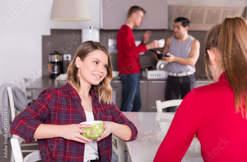 Obraz Female talking to female friend at kitchen of hostel - fototapety do salonu