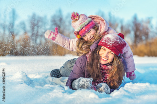 Obraz Little girl and her mother playing outdoors at sunny winter day. Active winter holydays concept. - fototapety do salonu