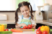 Happy Child Girl Chopping Tomatoes On Cutting Board With Knife In Kitchen