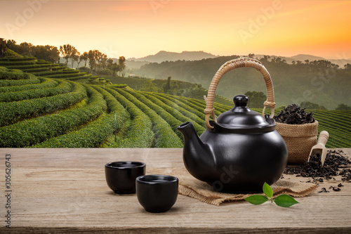 Spoed Foto op Canvas Thee Cup of hot tea with teapot, green tea leaves and dried herbs on the wooden table in plantations background with empty space, Organic product from the nature for healthy with traditional