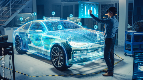 Automotive Engineer Use Virtual Reality Headset for Virtual Electric Car 3D Model Design Analysis and Improvement. 3D Graphics Visualization Shows Fully Developed Vehicle Prototype Analysed Optimized - 305628557