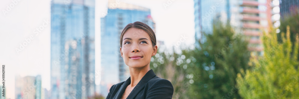 Fototapeta Asian confident business woman looking up to the bright future of her career opportunities. Job, work aspirational banner panorama background. Businesspeople lifestyle.