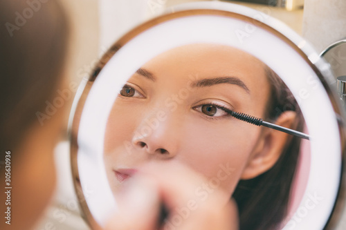 Woman applying make up beauty product putting mascara in ring lighted round makeup mirror at home bathroom morning routine. Beautiful Asian lady getting ready applying eye make-up with brush.