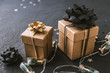 Christmas gifts with a gold and black bow on a black background.