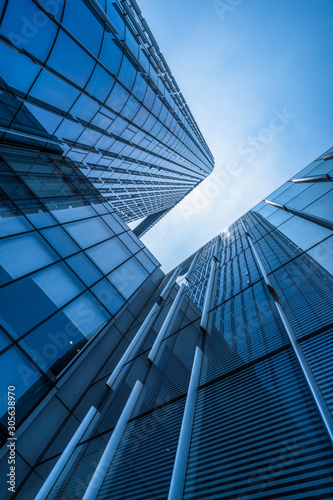 Bottom view of modern skyscrapers in business district against blue sky Tablou Canvas