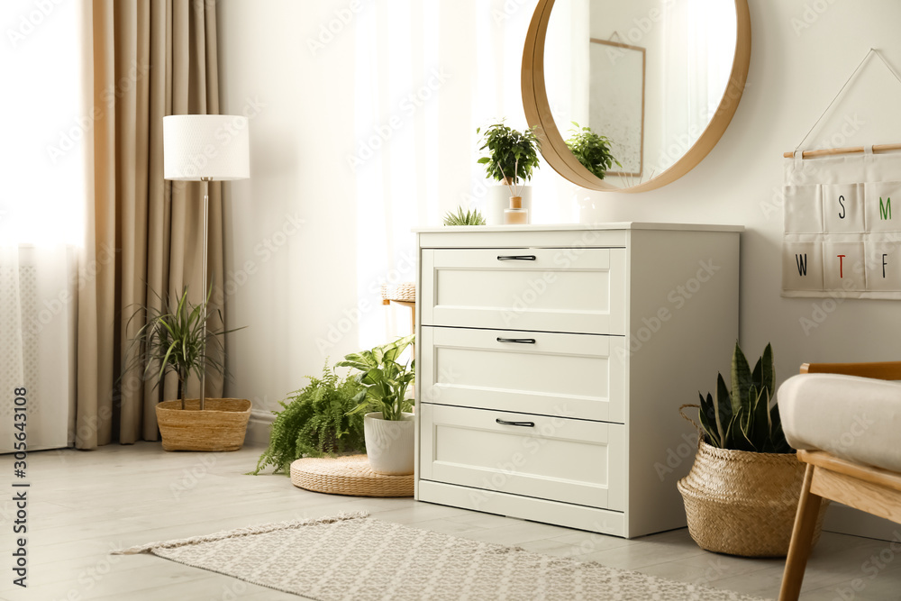 Fototapeta Stylish room interior with chest of drawers and round mirror