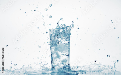 one glass of water with splash from falling ice cube  white background  isolated object