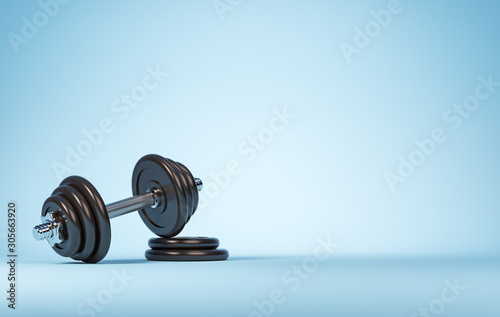 Heavy black professional dumbbell for fitness and bodybuilding with two weight plates on the blue background.