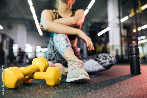 young couple sitting on bench,Young sports girls are engaged in fitness, lifestyle, sports and healthy eating, in the gym girls do exercises - 305664722