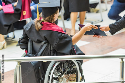 Obraz student in wheelchair receives a diploma from a university. disabled girl with a diploma from school and university. - fototapety do salonu
