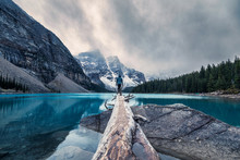 Traveler Standing On Log In Maraine Lake On Gloomy Day At Banff National Park