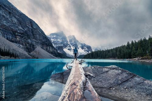 Fotografie, Obraz Traveler standing on log in Maraine lake on gloomy day at Banff national park
