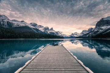 Traveler relaxing on wooden pier in Maligne lake at Spirit island, Jasper national park