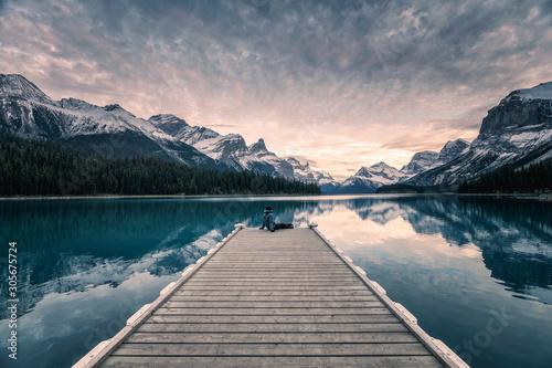 Foto auf AluDibond Grau Traveler relaxing on wooden pier in Maligne lake at Spirit island, Jasper national park